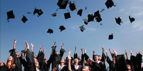 Students after graduation, flying away their graduation hats.